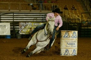 woman barrel racing on gray horse