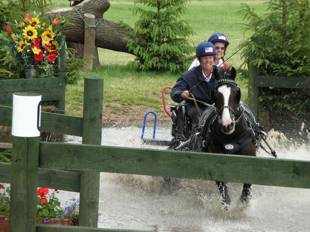 woman on black horse cantering through water to jump over fence
