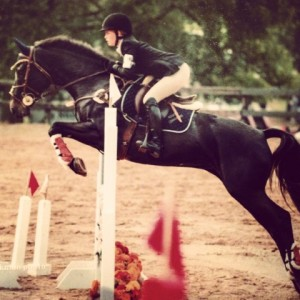 girl jumping black horse over fence