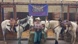 woman standing with two gray horses in front of triple crown sign