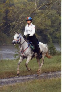 woman riding gray horse on path