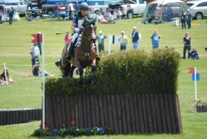 woman jumping bay horse over jump at rolex