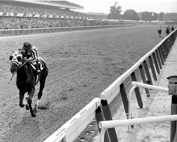 Aged photo of Secretariat pulling away from other horses on the track