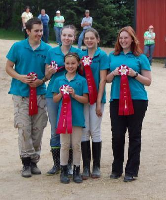 members of pony club holding their ribbons