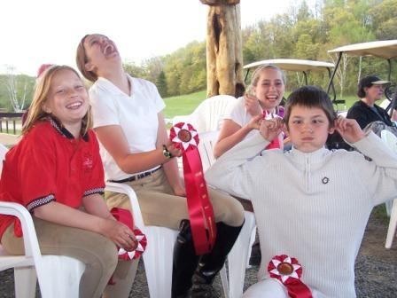 members of pony club laughing and holding ribbons