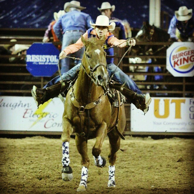 Woman barrel racing on chesnut horse