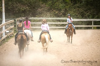 Four girls riding in the arena