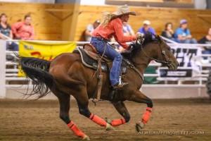 girl barrel racing on bay horse