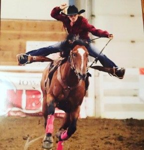 Woman barrel racing bay horse