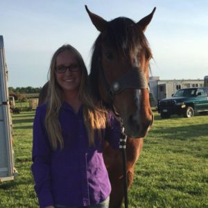 girl standing with bay horse