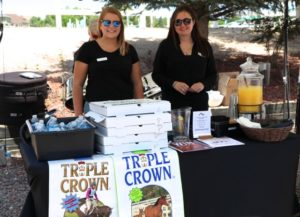 two women standing at Triple Crown booth
