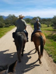 hind view of father and daughter trail riding