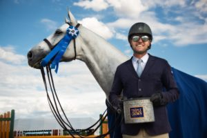 Man standing with gray horse and holding triple crown prize